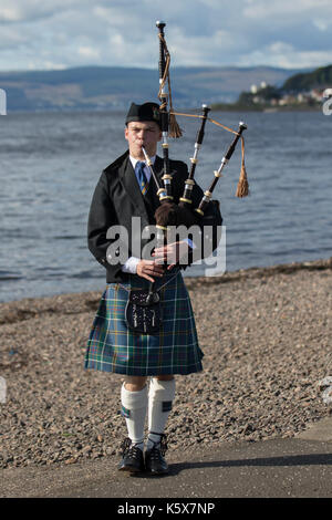 Scottish Piper playing the bagpipes on the beach at Largs. Firth of Clyde, Scotland, UK - Stock Photo