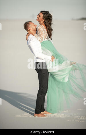Groom lifted his bride in his arms and hugged her. They standing on background of white sand in desert and laugh - Stock Photo