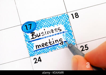 Woman fingers with pen writing reminder Business meeting in calendar. Close-up. - Stock Photo