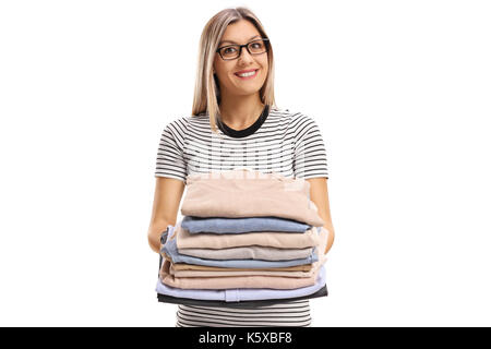 Young woman holding a pile of ironed and packed clothes isolated on white background - Stock Photo