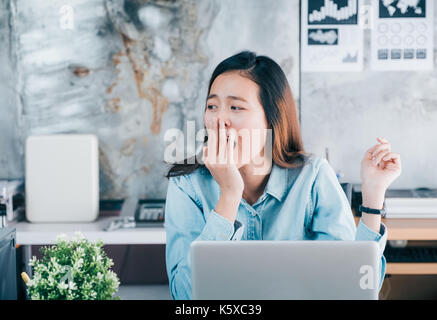 Young asian casual businesswoman yawn in front of laptop computer and looking through office window with bored feeling - Stock Photo