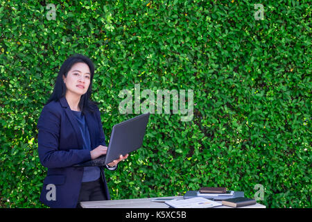 Asian Busineswoman using laptop computer working outside office at green hedge,Moblie office concept. - Stock Photo