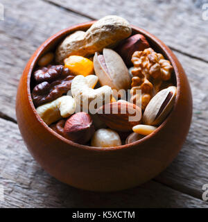 Mixed nuts in wooden bowl - Stock Photo