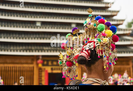 a view of girl's back, who is Dong ethnic minority in traditional dress in front of drum tower during the festival, - Stock Photo