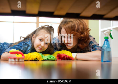 Mother and daughter do the cleaning in the house. Happy woman and little child girl wiped the floor. - Stock Photo