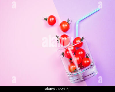 Tomato juice or smoothie, cherry tomato in drink glass with straw - Stock Photo