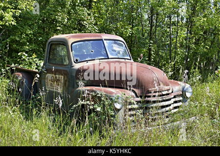 Old abandoned Cheverolet pickup truck sitting in a field - Stock Photo