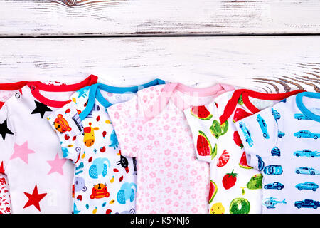 66a44864c7b Set of brand natural baby bodysuits. Newborn kids fashion summer rompers on  white wooden background