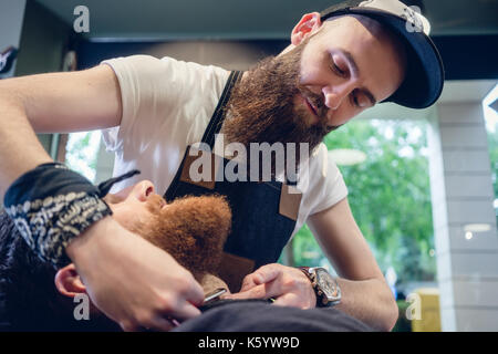 Bearded young man ready for shaving in the hair salon of a skill - Stock Photo