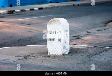 Stone road sign in Cuba showing distances to cities Holguin and Bayamo. - Stock Photo