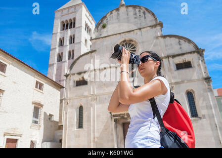 Pretty female tourist taking pictures. - Stock Photo