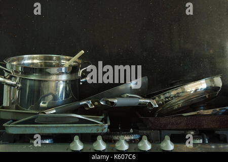 An horizontal image of a pile of dirty pans stacked on a greasy gas stove top in front of a black background. - Stock Photo