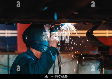 Man in a mask does welding machines. - Stock Photo