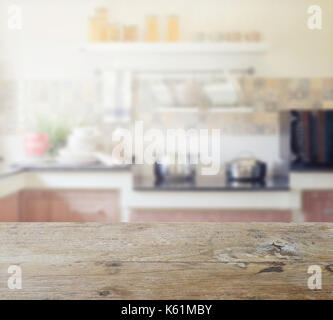 wooden table top with blur of modern kitchen interior for background - Stock Photo