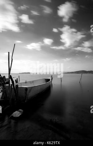 A small fishing boat on a lake, with perfectly still water and moving clouds - Stock Photo