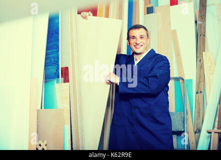 smiling man wearing protective workwear standing with plywood in store - Stock Photo