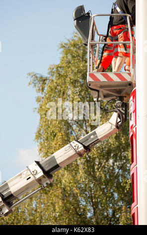 Workers in aerial work platform tending to sign. - Stock Photo