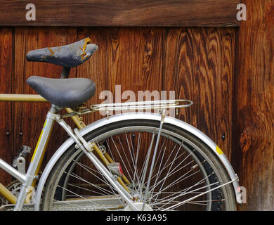 Old bike against the wooden wall of old house in Asia. - Stock Photo