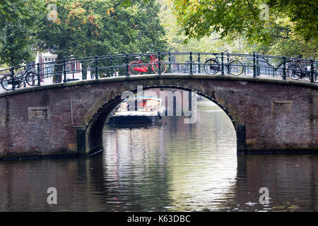 Canal and a red bike parked on a bridge in Amsterdam - Stock Photo