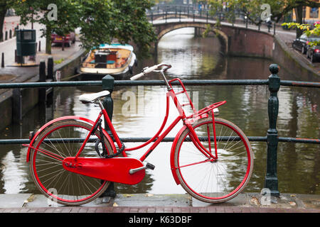 Red bike on a bridge over a canal in Amsterdam - Stock Photo