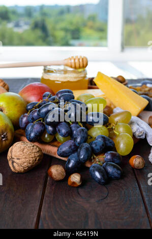 A set of products: grapes, nuts, honey, pears, cheese on a dark wooden table near the window. - Stock Photo