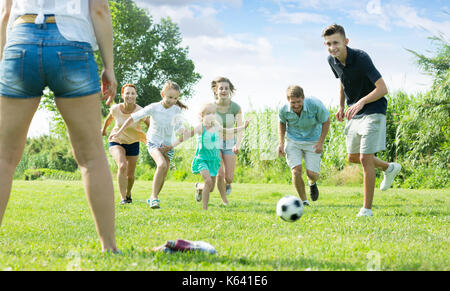Mother and father with glad kids playfully running after ball outdoors on green lawn in park. Focus on boy - Stock Photo
