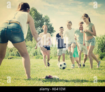 Adult family with four kids playfully running after ball outdoors on green lawn in park. Focus on teenager girl - Stock Photo