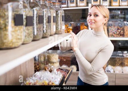 Young glad woman standing next to jars with dried herbs and picking selected in organic store - Stock Photo