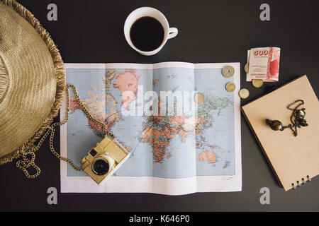 Planning the trip. World map with the hat, film camera, some money, notebook from recycled paper and freshly brewed - Stock Photo