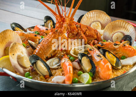 Gourmet seafood Valencia paella with fresh langoustine, clams, mussels and squid on savory saffron rice with prawn, - Stock Photo