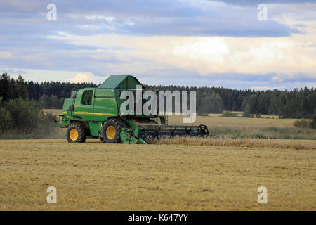SALO, FINLAND - AUGUST 25, 2017: Farmer harvests grain with John Deere Combine 9460i on an autumn evening in rural - Stock Photo