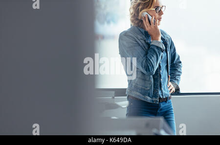 Businesswoman standing in workplace and talking on cellphone. Serious young female standing in office using mobile - Stock Photo