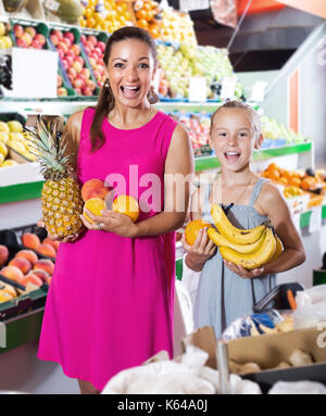 Excited young woman with girl looking satisfied in fruit store - Stock Photo