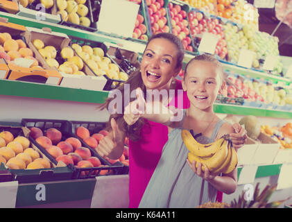 portrait of happy young woman with daughter looking excited on fruit market - Stock Photo