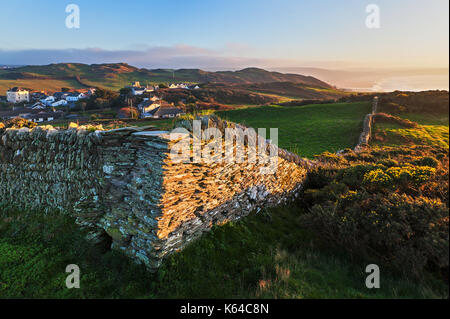 Corner of a dry stone wall in a North Devon field with views of Mortehoe village  and Woolacombe bay in the background - Stock Photo
