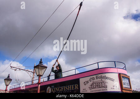 Seaton, Devon, UK. 11th Sept, 2017. UK Weather. A tram driver moves the trolley pole into place before taking tourists - Stock Photo
