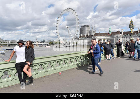 London, UK. 11th Sep, 2017. UK Weather: Tourists enjoy the sunshine on Westminster Bridge during changeable weather - Stock Photo