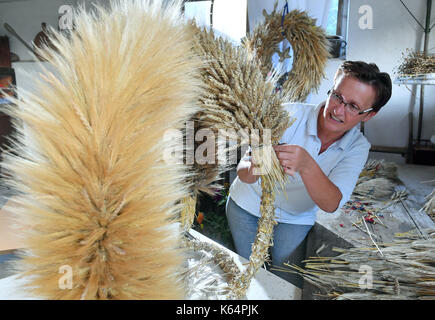 Wittenberg, Germany. 28th Aug, 2017. Kathrin Ahlers ties her harvest crown in a barn at the horse farm Ahlers in - Stock Photo