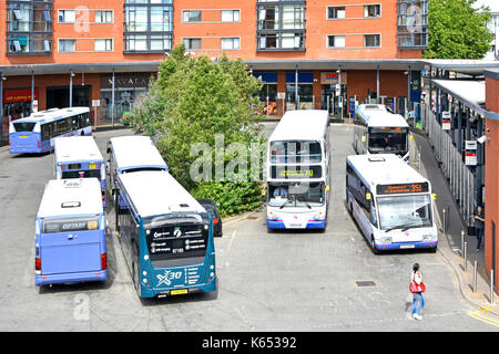 View from above looking down at buses Chelmsford town centre bus station which includes small selection of retail - Stock Photo