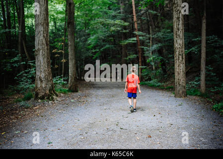 A boy walks on a dirt path in the woods. - Stock Photo