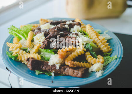 A plate of a steak salad with french fries or chips. - Stock Photo