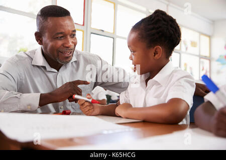 Teacher helping elementary school girl at her desk, close up - Stock Photo