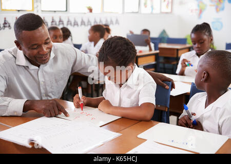 Teacher helping elementary school girl at her desk in class - Stock Photo