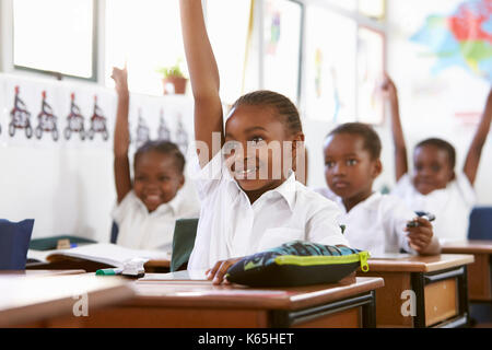 Kids raising hands during a lesson at an elementary school - Stock Photo