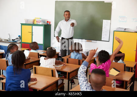 Teacher and kids with hands up in an elementary school class - Stock Photo
