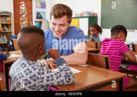 White male teacher helping elementary school boy in class - Stock Photo