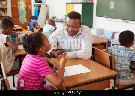 Black male teacher helping elementary school girl in class - Stock Photo