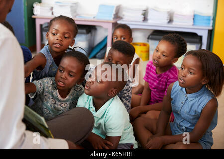 Teacher reading book to elementary school children in class - Stock Photo