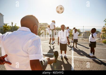 Boy kicking ball to classmates in elementary school playground - Stock Photo