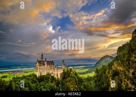 Neuschwanstein Castle at sunrise, seen from the bridge Marienbrücke, built high above the Pöllat Gorge - Stock Photo